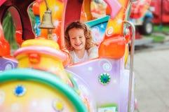Ευτυχές οδηγώντας τραίνο κοριτσιών παιδιών στο funfair στις θερινές διακοπές Στοκ Εικόνες