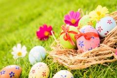 Ευτυχές Πάσχα! Ζωηρόχρωμα αυγά Πάσχας κινηματογραφήσεων σε πρώτο πλάνο στη φωλιά στοκ φωτογραφίες