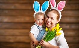 Ευτυχές Πάσχα! μητέρα και μωρό στα αυτιά κουνελιών με τα κίτρινα λουλούδια Στοκ Εικόνες