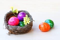 Ευτυχές Πάσχα! Μια φωλιά Πάσχας με τα ζωηρόχρωμα αυγά Πάσχας και primroses Στοκ φωτογραφία με δικαίωμα ελεύθερης χρήσης