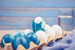 Ευτυχές Πάσχα, το οργανικό μπλε αυγό Πάσχας που στέκεται στα άσπρα αυγά χρώματος περιμένει τη ζωγραφική, διακοσμήσεις διακοπών Πά Στοκ Εικόνες