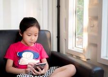 Ευτυχές παιδί, ασιατικό παιδί μωρών που παίζει το έξυπνο τηλέφωνο Στοκ Εικόνες