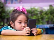 Ευτυχές παιδί, ασιατικό παιδί μωρών που παίζει το έξυπνο τηλέφωνο garde Στοκ Εικόνες