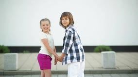 Ευτυχές παιδί δύο Κρατούν τα χέρια και ξετυλίγουν το χαμόγελο και το γέλιο απόθεμα βίντεο