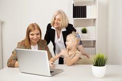 Ευτυχές παιδί με τη γιαγιά και τη μητέρα που χρησιμοποιούν το lap-top από κοινού στοκ φωτογραφίες