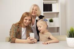 Ευτυχές παιδί με τη μητέρα και τη γιαγιά που φαίνονται τηλέφωνο στο δωμάτιο και το χαμόγελο στοκ φωτογραφία