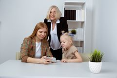 Ευτυχές παιδί με τη μητέρα και τη γιαγιά που φαίνονται τηλέφωνο στο δωμάτιο και το χαμόγελο στοκ εικόνες