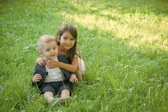 Ευτυχές παιδί που έχει τη διασκέδαση Οικογένεια, παιδιά, αδελφός και αδελφή στην πράσινη χλόη Στοκ Εικόνες