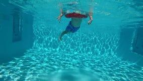 Ευτυχές παιδί που έχει τη διασκέδαση στην μπλε σαφή λίμνη απόθεμα βίντεο