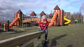 Ευτυχές παιδί που αισθάνεται καλό rocker στην καρέκλα στην παιδική χαρά στο πάρκο, ζωηρόχρωμη παιδική ηλικία φιλμ μικρού μήκους