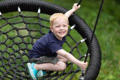 Ευτυχές παιδί που κάθεται σε μια ταλάντευση στοκ εικόνα με δικαίωμα ελεύθερης χρήσης