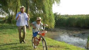 Ευτυχές παιδί που μαθαίνει να οδηγά το ποδήλατο με τη βοήθεια του γονέα του σε αγροτικό στην υπαίθρια φύση υποβάθρου απόθεμα βίντεο