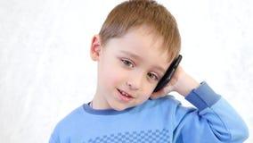 Ευτυχές παιδί που μιλά ευτυχώς σε ένα κινητό τηλέφωνο σε ένα άσπρο υπόβαθρο, που παρουσιάζει ένα χαμόγελο και θετικές συγκινήσεις απόθεμα βίντεο