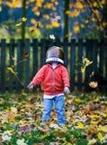 Ευτυχές παιδί που ρίχνει τα φύλλα επάνω στον αέρα στοκ εικόνες