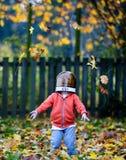Ευτυχές παιδί που ρίχνει τα φύλλα στοκ φωτογραφία