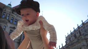 Ευτυχές παιδί σε μια ΚΑΠ στο υπόβαθρο του μπλε ουρανού στο backlight, παιχνίδια μητέρων με το νέο γιο στην οδό φιλμ μικρού μήκους