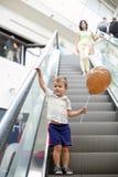 Ευτυχές παιδί στην κυλιόμενη σκάλα στο εμπορικό κέντρο Μικρό παιδί που κρατά το καφετί μπαλόνι στοκ εικόνες