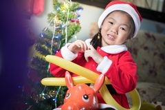 Ευτυχές παιδί στο καπέλο santa με ένα δώρο κοντά στο χριστουγεννιάτικο δέντρο, CH Στοκ Εικόνα