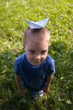 Ευτυχές παιδικό παιχνίδι γέλιου με το σκάφος εγγράφου στο εσωτερικό Πράσινη ανασκόπηση πεδίων Ευτυχής παιδική ηλικία, καλοκαίρι,  στοκ εικόνες με δικαίωμα ελεύθερης χρήσης
