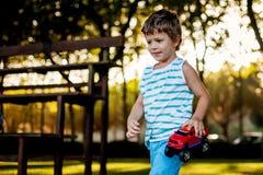 Ευτυχές παιχνίδι αγοριών με το αυτοκίνητο σφαιρών και παιχνιδιών στην πράσινη χλόη στοκ εικόνες