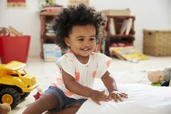 Ευτυχές παιχνίδι κοριτσάκι με τα παιχνίδια στο χώρο για παιχνίδη Στοκ φωτογραφία με δικαίωμα ελεύθερης χρήσης