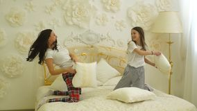 Ευτυχές παιχνίδι κορών οικογενειακών μητέρων και παιδιών στην πάλη κρεβατιών και μαξιλαριών φιλμ μικρού μήκους