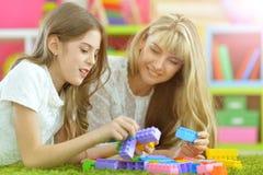 Ευτυχές παιχνίδι μητέρων με την κόρη της στο σχεδιαστή Στοκ Φωτογραφία