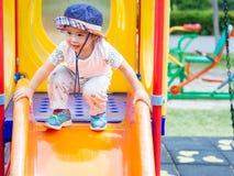 Ευτυχές παιχνίδι μικρών κοριτσιών στην παιδική χαρά Παιδιά, ευτυχή, FA στοκ εικόνα