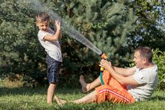 Ευτυχές παιχνίδι πατέρων και γιων στον κήπο στο χρόνο ημέρας Στοκ Εικόνες