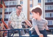 Ευτυχές παιχνίδι πατέρων με το μικρό παιδί στην παιδική χαρά στοκ εικόνες