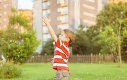 Ευτυχές παιχνίδι αγοριών με τις φυσαλίδες σαπουνιών στο πάρκο Στοκ Εικόνες