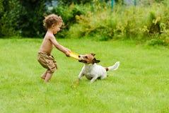 Ευτυχές παιχνίδι αγοριών με το ενεργό παιχνίδι σκυλιών στο χορτοτάπητα Στοκ φωτογραφία με δικαίωμα ελεύθερης χρήσης