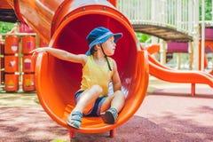 Ευτυχές παιχνίδι αγοριών παιδάκι στη ζωηρόχρωμη παιδική χαρά Λατρευτό παιδί που έχει τη διασκέδαση υπαίθρια Στοκ Εικόνες