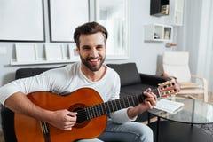 Ευτυχές παιχνίδι ατόμων στην κιθάρα εξέταση τη κάμερα Στοκ Εικόνες