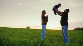 Ευτυχές παιχνίδι γονέων με το γιο ενός έτους Ένας υγιής πατέρας ρίχνει το γιο επάνω, στάσεις Mom δίπλα σε τον Ευτυχής οικογένεια  φιλμ μικρού μήκους