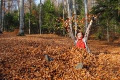 Ευτυχές παιχνίδι γυναικών με τα φύλλα φθινοπώρου στοκ εικόνες