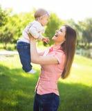 Ευτυχές παιχνίδι γυναικών Youmg με το χαριτωμένο μωρό της στο θερινό ηλιόλουστο πάρκο υπαίθριο Εικόνα Mothercare Στοκ φωτογραφία με δικαίωμα ελεύθερης χρήσης