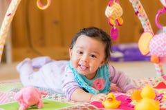 Ευτυχές παιχνίδι κοριτσάκι χαμόγελου με τα παιχνίδια Στοκ φωτογραφία με δικαίωμα ελεύθερης χρήσης