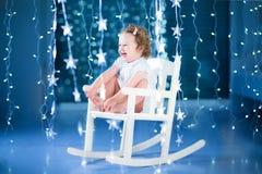 Ευτυχές παιχνίδι κοριτσιών μικρών παιδιών γέλιου σε μια άσπρη λικνίζοντας καρέκλα μέσα Στοκ Εικόνα