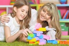Ευτυχές παιχνίδι μητέρων με την κόρη της στο σχεδιαστή Στοκ Εικόνες