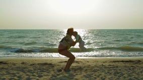Ευτυχές παιχνίδι μητέρων με το αγοράκι στην παραλία απόθεμα βίντεο