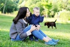 Ευτυχές παιχνίδι μητέρων με το γιο της στο πάρκο Στοκ Εικόνα
