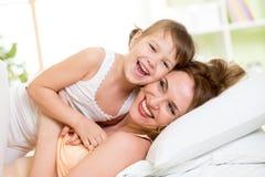 Ευτυχές παιχνίδι μητέρων με το παιδί στην απόλαυση κρεβατιών Στοκ φωτογραφία με δικαίωμα ελεύθερης χρήσης