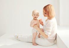 Ευτυχές παιχνίδι μητέρων με το σπίτι μωρών στο λευκό Στοκ Εικόνες