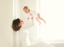 Ευτυχές παιχνίδι μητέρων χαμόγελου με το σπίτι μωρών στο λευκό Στοκ Εικόνες