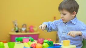 Ευτυχές παιχνίδι μικρών παιδιών με τα πλαστικά μαχαιροπήρουνα στον πίνακα απόθεμα βίντεο