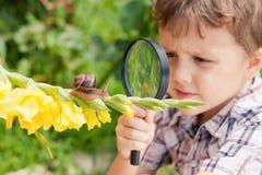 Ευτυχές παιχνίδι μικρών παιδιών στο πάρκο με το σαλιγκάρι στο χρόνο ημέρας στοκ φωτογραφίες