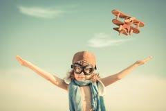 Ευτυχές παιχνίδι παιδιών με το αεροπλάνο παιχνιδιών Στοκ Εικόνα