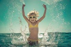 Ευτυχές παιχνίδι παιδιών στη θάλασσα Στοκ Φωτογραφία