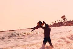 Ευτυχές παιχνίδι πατέρων και παιδιών στην παραλία στο καλοκαίρι sunse Στοκ Φωτογραφία